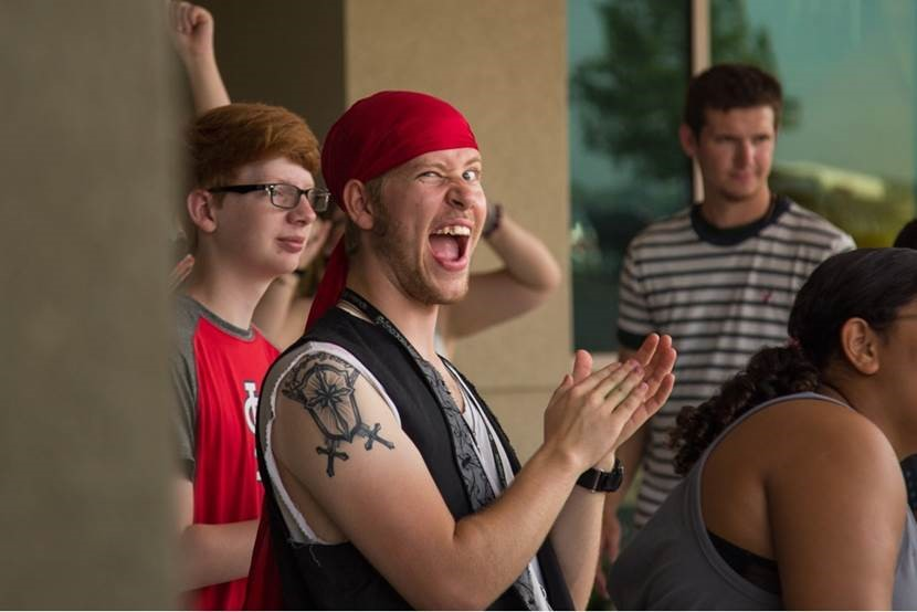 Camp Counselor dressed as pirate claps as campers arrive to their day camp!