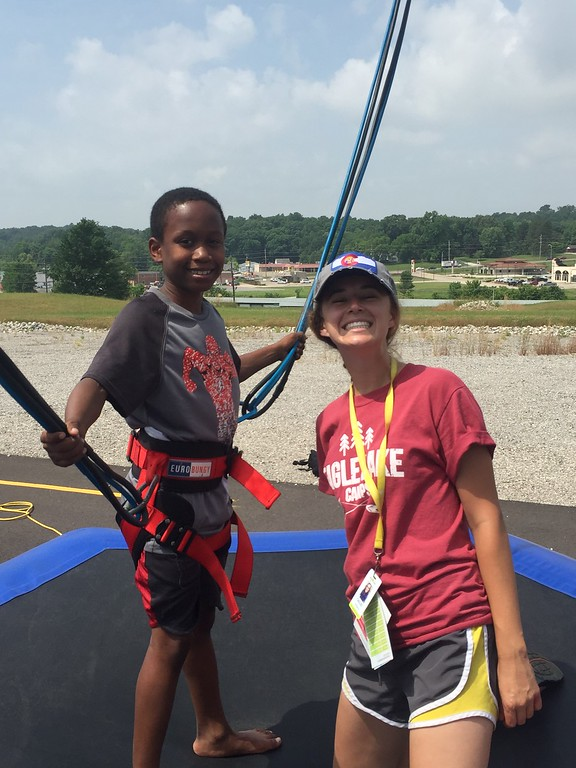 Eagle Lake Camp Counselor helps camper jump on the Bungee Trampoline!