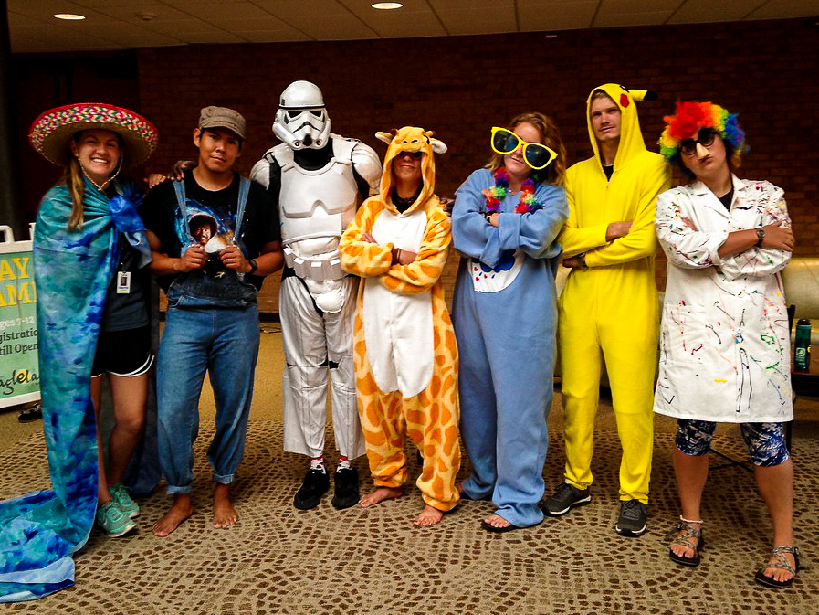 Camp Counselors dress up as a giraffe, farmer, storm trooper, and Pokemon.