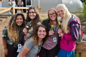 Camp Counselors pose with flowers in front of Thunder Dome.